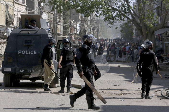 Police officers chase angry supporters of Tehreek-e-Labiak Pakistan, a radical Islamist political party, during a clash following the arrest of their party leader Saad Rizvi, in Karachi, Pakistan, Tuesday, April 13, 2021. Two demonstrators and a policeman were killed Tuesday in violent clashes between Islamists and police in Pakistan, hours after authorities arrested Rizvi in the eastern city of Lahore, a senior official and local media reported. (AP Photo/Fareed Khan)