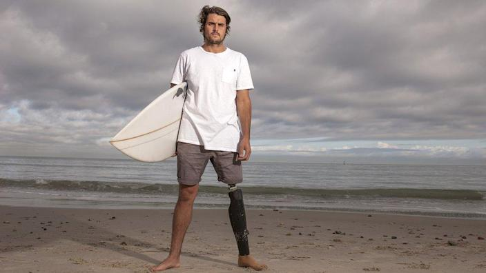 Chris Bowes on the beach with a surfboard