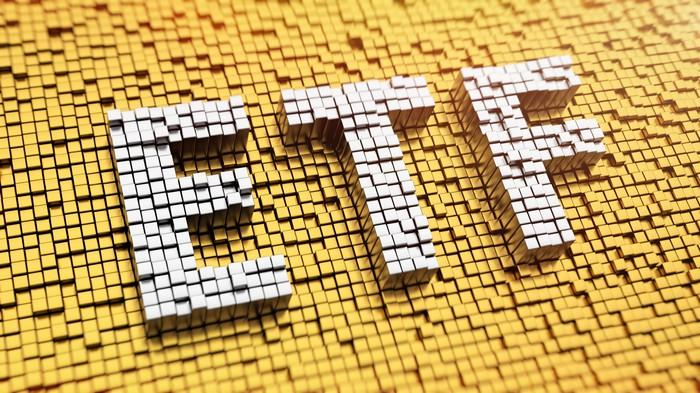 ETF spelled in white mosaic against a gold mosaic background.
