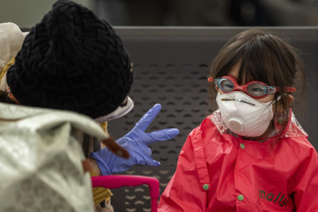 A woman plays with her daughter as they wait at Barcelona airport, Spain, Saturday, March 14, 2020. Spain's prime minister has announced a two-week state of emergency from Saturday in a bid to contain the new coronavirus outbreak. For most people, the new coronavirus causes only mild or moderate symptoms. For some, it can cause more severe illness, especially in older adults and people with existing health problems. (AP Photo/Emilio Morenatti)