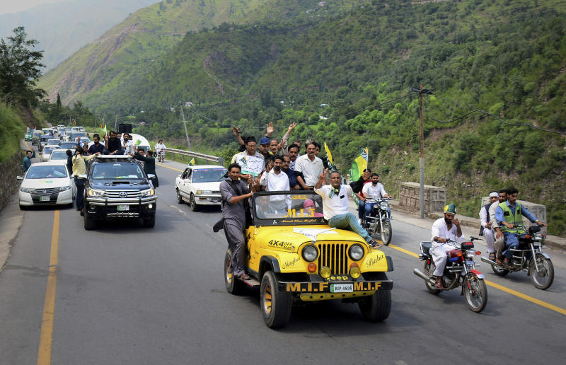 Journalists make victory signs while take part in a rally marching towards the Line of Control, which divides the Himalayan region, in Chinari, a small of Pakistani control's Kashmir, Saturday, Aug. 24, 2019. Pakistani police have stopped hundreds of journalists from symbolically trying to cross the highly militarized border into Indian-controlled Kashmir. (AP Photo/M.D. Mughal)