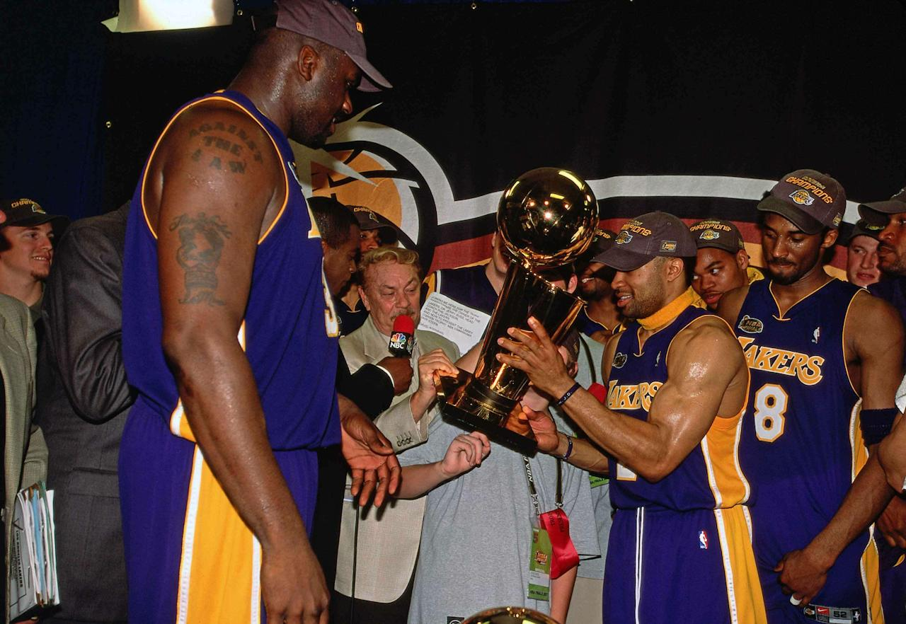 <p>\PHILADELPHIA - JUNE 15: Derek Fisher #2 and Shaquille O'Neal #34 of Los Angeles Lakers present Lakers owner Jerry Buss with the Championship trophy after winning the NBA Title by defeating the Philadelphia 76ers in Game 5 of the 2001 NBA Finals played June 15, 2001 at the First Union Center in Philadelphia, Pennsylvania. NOTE TO USER: User expressly acknowledges that, by downloading and or using this photograph, User is consenting to the terms and conditions of the Getty Images License agreement. Mandatory Copyright Notice: Copyright 2001 NBAE (Photo by Nathaniel S. Butler/NBAE via Getty Images)</p>