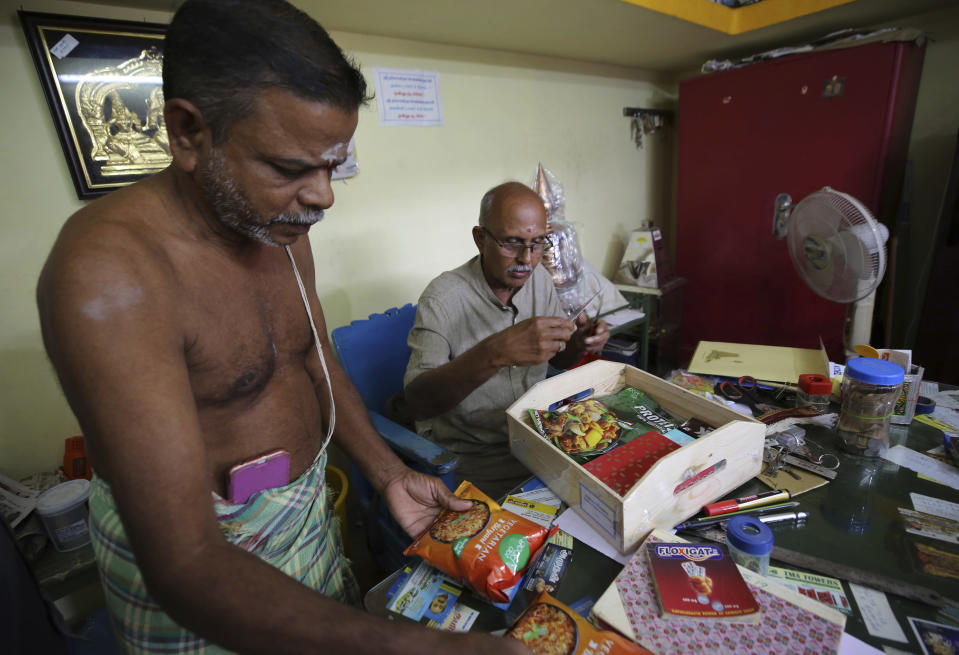 A Hindu priest, left, and a temple official open a box full of packaged food and sweets sent by a non-government organization to be distributed among villagers ahead of the inauguration of U.S. Vice President-elect Kamala Harris, in Thulasendrapuram, the hometown of Harris' maternal grandfather, south of Chennai, Tamil Nadu state, India, Tuesday, Jan. 19, 2021. The inauguration of President-elect Joe Biden and Vice President-elect Kamala Harris is scheduled be held Wednesday. (AP Photo/Aijaz Rahi)