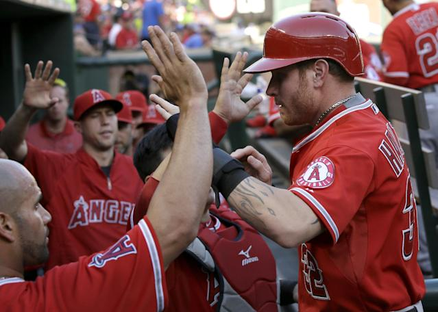 Los Angeles Angels' Josh Hamilton, right, is greeted in the dugout by Albert Pujols, left, and teammates after scoring on a Howie Kendrick sacrifice fly out in the first inning of a baseball game, Thursday, July 10, 2014, in Arlington, Texas. (AP Photo/Tony Gutierrez)