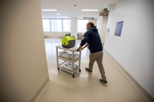 Vaccine team lead Ruben Rodriguez pushes a trolly of supplies, including doses of the Moderna COVID-19 vaccine, through Humber River Hospital on May 4.