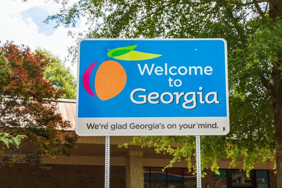 "a blue ""Welcome to Georgia"" sign in front of trees and a building"