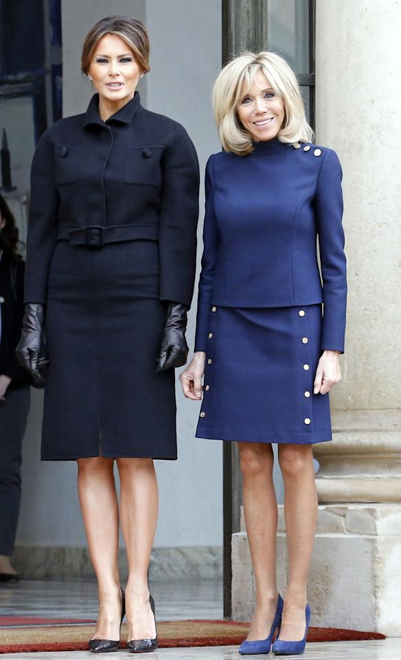 <p>Melania Trump wears a navy jacket by Bottega Veneta as she is greeted by the First Lady of France, Brigitte Macron, at the Elysee Presidential Palace. </p>