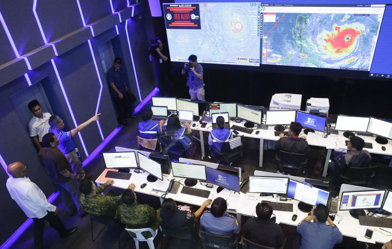 Philippine President Rodrigo Duterte, second from left, observes the National Disaster Risk Reduction and Management Council operation center in metropolitan Manila, Philippines on Thursday, Sept. 13, 2018. The Philippine officials have begun evacuating thousands of people in the path of the most powerful typhoon this year, closing schools and readying bulldozers for landslides. (AP Photo/Aaron Favila)