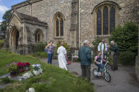 """The Rev. Jonathan Gordon, second right, and Assistant Vicar Miranda Sheldon, second left, greet Anglican worshippers who attended their first communal prayer service after pandemic restrictions were eased, at St. Mary's Church in Northchurch, England, on Sunday, July 5, 2020. On March 24, the Church of England closed all its buildings. """"It posed an immediate and immense challenge,"""" Gordon says. """"It meant that we had to completely rethink how we did everything."""" (AP Photo/Elizabeth Dalziel)"""
