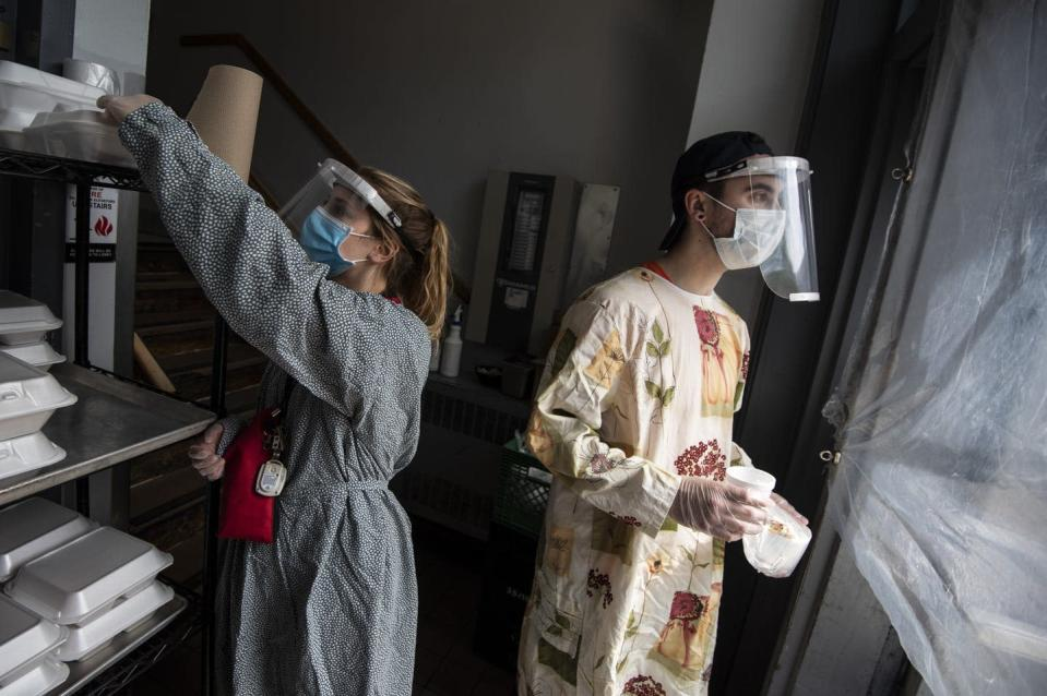 """<span class=""""caption"""">Staff members wear gloves, face shields and gowns as they hand out meals at lunchtime at the Shepherds of Good Hope soup kitchen in Ottawa in 2020. </span> <span class=""""attribution""""><span class=""""source"""">THE CANADIAN PRESS/Justin Tang </span></span>"""