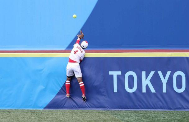 PHOTO: Yuka Ichiguchi #4 of Team Japan reaches but can't catch the ball going over the right field fence hit by Kelsey Stewart #7 of Team United States for a walk-off home run in the eighth inning during softball opening round. (Yuichi Masuda/Getty Images)