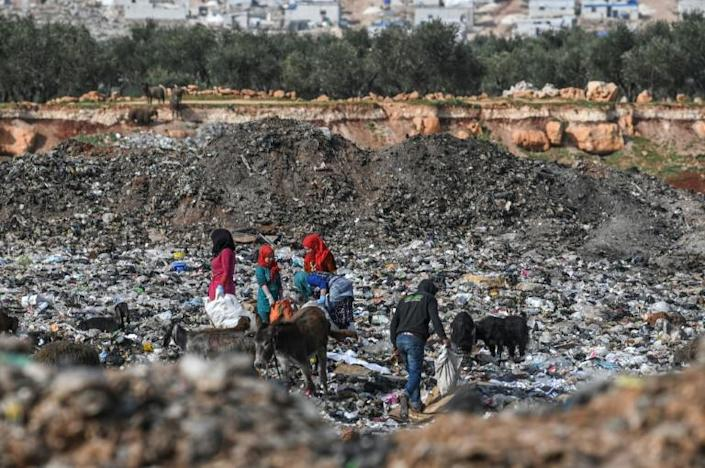 Syrians rummage through a landfill in Kafr Lusin village on the border with Turkey in Syria's Idlib on March 10 (AFP Photo/Ozan KOSE)