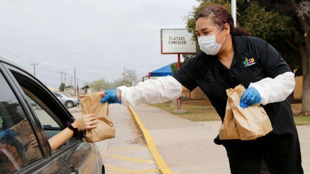 PHOTO: Burleson Elementary School's cafeteria manager Geneva Garcia hands a sack lunch to a family outside a school building in Odessa, Texas, March 17, 2020. (Ben Powell/Odessa American via AP, FILE)