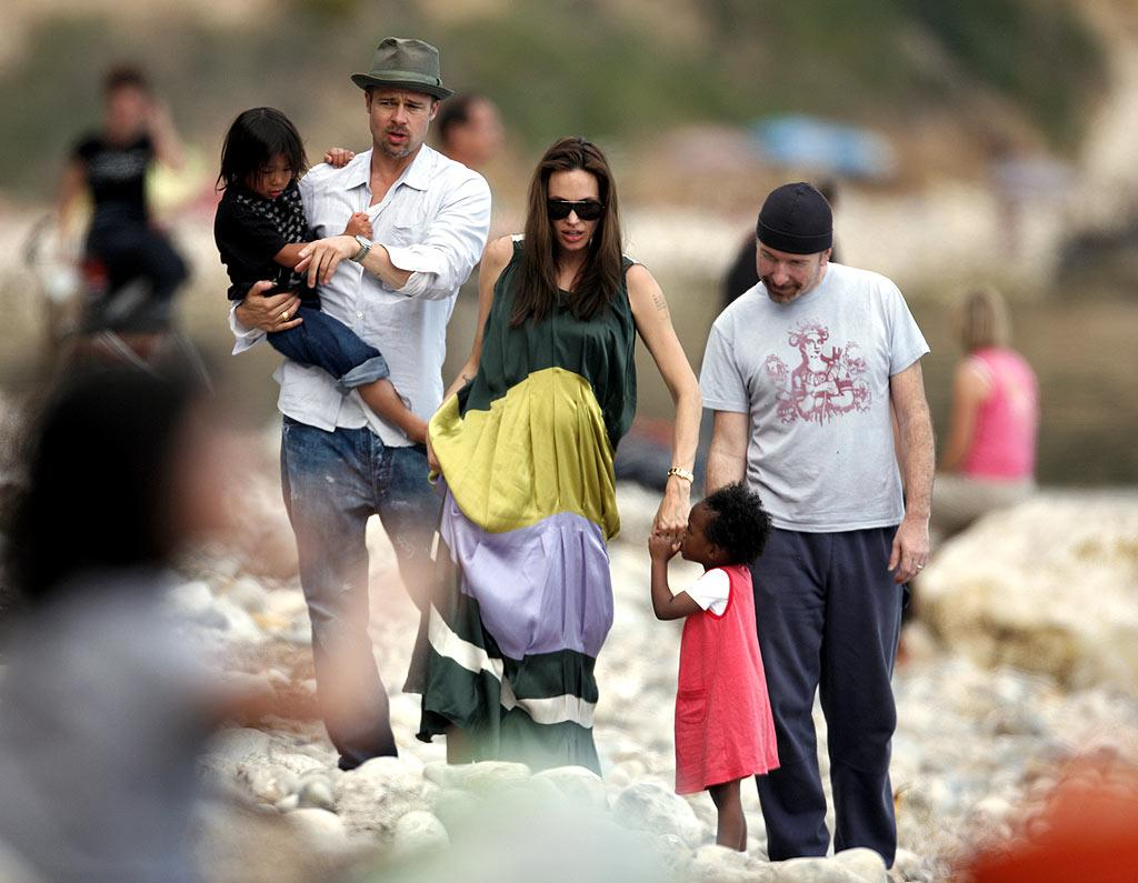 "Brad Pitt, Angelina Jolie, and their clan enjoyed a day at the beach in Eze, France last Sunday. And yes, that's family friend and U2 guitarist The Edge playing babysitter! PapaPress/MacFarlane/<a href=""http://www.splashnewsonline.com"" target=""new"">Splash News</a> - May 4, 2008"
