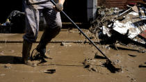 A resident sweeps mud from his house after flooding in Drolenvol, Belgium, Saturday, July 17, 2021. Residents in several provinces were cleaning up after severe flooding in Germany and Belgium turned streams and streets into raging torrents that swept away cars and caused houses to collapse. (AP Photo/Virginia Mayo)
