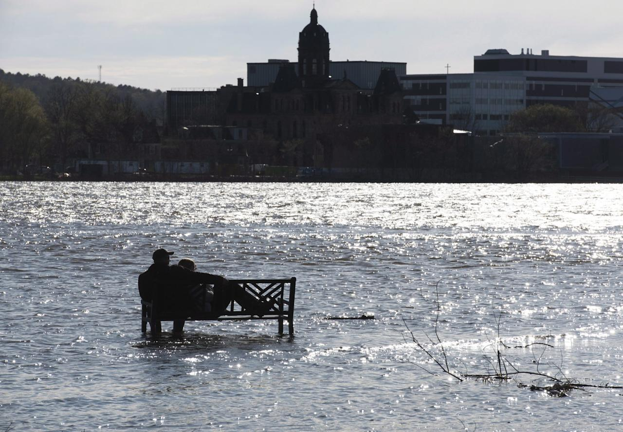 <p>This couple didn't have to fight for a seat since they were the only ones to wade through the flood water from the St. John River to get to this bench in Carleton Park on the north side of Fredericton, NB, on Sunday, May 7, 2017. Photo from CP Images </p>