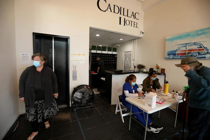 """Wendy Brown waits for the elevator in the lobby of the Cadillac Hotel in Venice. Those staying at the hotel have their temperature taken upon entrance by nurses. <span class=""""copyright"""">(Genaro Molina / Los Angeles Times)</span>"""