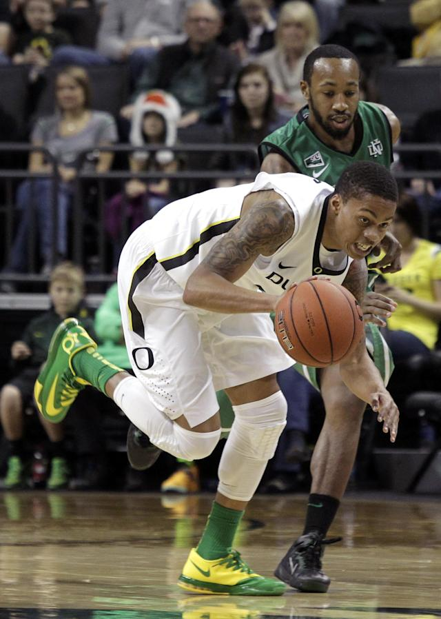 Oregon guard Joseph Young, front, drives downcourt ahead of North Dakota guard Jamal Webb during the first half of an NCAA college basketball game in Eugene, Ore., Saturday, Nov. 30, 2013. (AP Photo/Don Ryan)