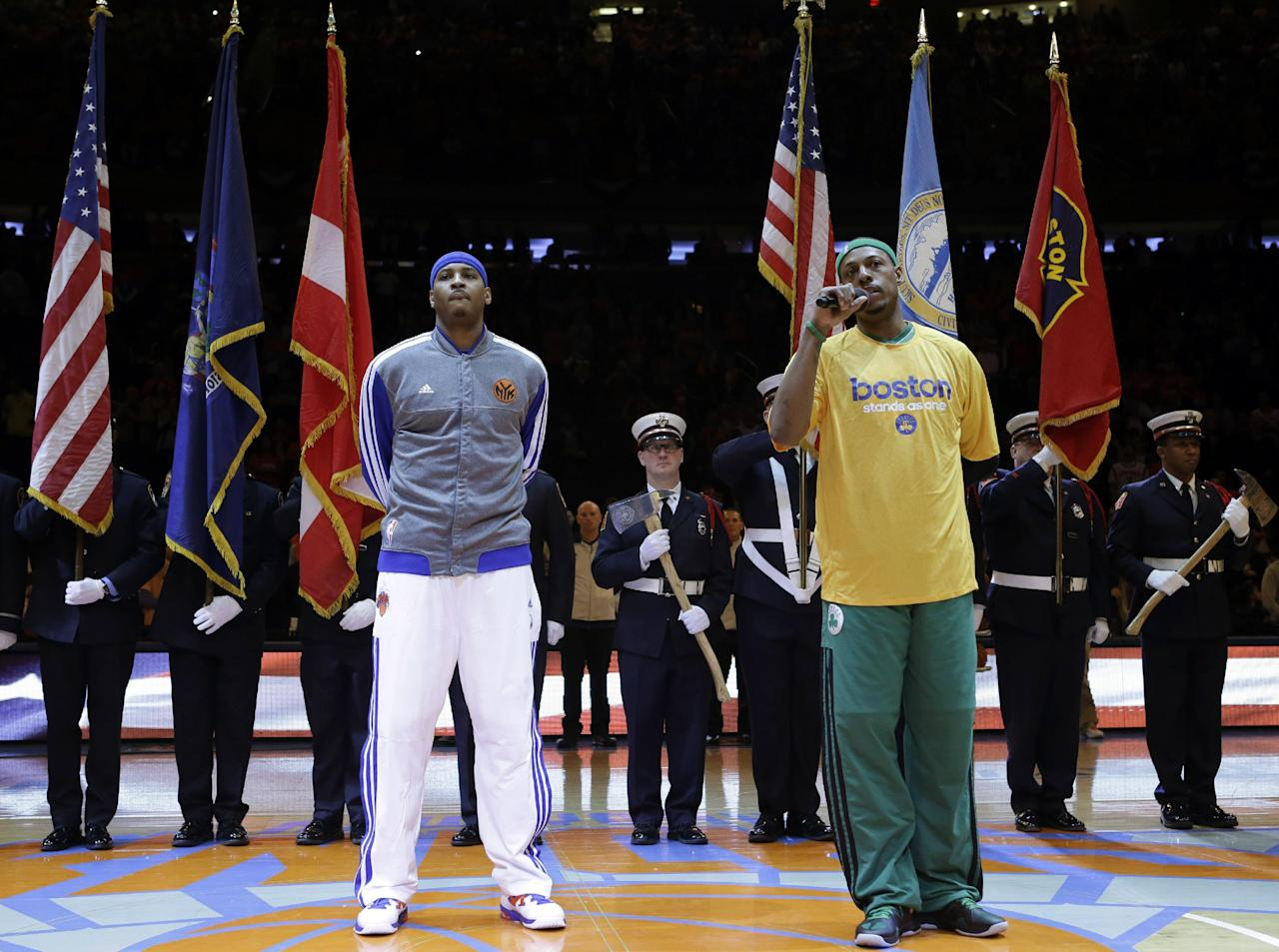 New York Knicks forward Carmelo Anthony, left, listens as Boston Celtics forward Paul Pierce speaks about the Boston Marathon bombings in front of color guards from New York and Boston before Game 1 in the first round of the NBA basketball playoffs at Madison Square Garden in New York, Saturday, April 20, 2013. (AP Photo/Kathy Willens)