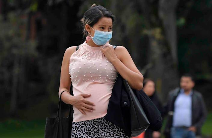 A pregnant woman wears a face mask as a preventative measure against the spread of the new coronavirus, COVID-19, as she waits for the bus in Bogota, on March 16, 2020. | RAUL ARBOLEDA/AFP via Getty Images