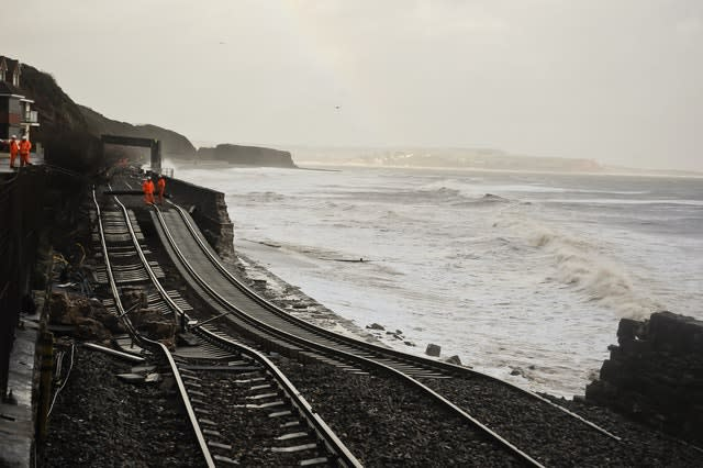 A huge length of railway track is exposed and left hanging after the sea wall collapsed in Dawlish in 2014