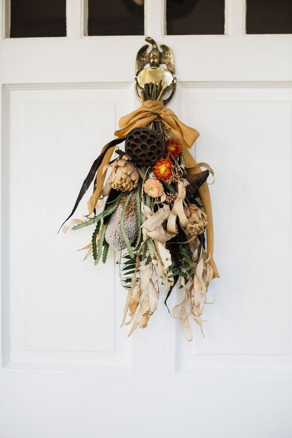 "<p>Save your wreaths for for the winter holidays; this smaller, <a href=""https://cheetahisthenewblack.com/living/lifestyle/diy-seasonal-door-swag/"" rel=""nofollow noopener"" target=""_blank"" data-ylk=""slk:seasonal door hanging"" class=""link rapid-noclick-resp"">seasonal door hanging</a> is ideal for Thanksgiving. Try using dried flowers or other greens you can find in your yard and tying them together with floral tape or twine.</p><p><a class=""link rapid-noclick-resp"" href=""https://go.redirectingat.com?id=74968X1596630&url=https%3A%2F%2Fwww.michaels.com%2Fyellow-natural-dried-floral-bouquet-by-ashland%2F10635166.html&sref=https%3A%2F%2Fwww.delish.com%2Fholiday-recipes%2Fthanksgiving%2Fg33808794%2Fthanksgiving-decorations%2F"" rel=""nofollow noopener"" target=""_blank"" data-ylk=""slk:BUY NOW"">BUY NOW</a><em><strong> Dried florals, $11.99</strong></em></p>"