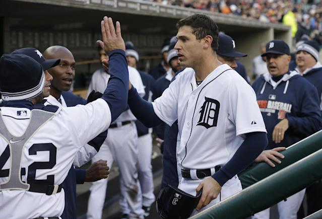 Detroit Tigers second baseman Ian Kinsler is congratulated in the dugout after scoring on a sacrifice by teammate Miguel Cabrera during the first inning of a baseball game against the Cleveland Indians in Detroit, Wednesday, April 16, 2014. (AP Photo/Carlos Osorio)