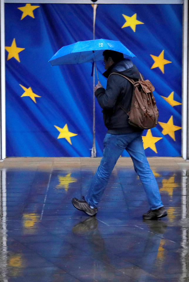 A man holds an umbrella as he walks past the flag of the European Union outside the European Commission in Brussels, Belgium, December 13, 2017. REUTERS/Phil Noble