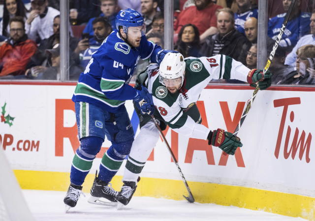 Vancouver Canucks' Tyler Motte, left, checks Minnesota Wild's Jordan Greenway during the first period of an NHL hockey game in Vancouver, British Columbia, Tuesday Dec. 4, 2018. (Darryl Dyck/The Canadian Press via AP)