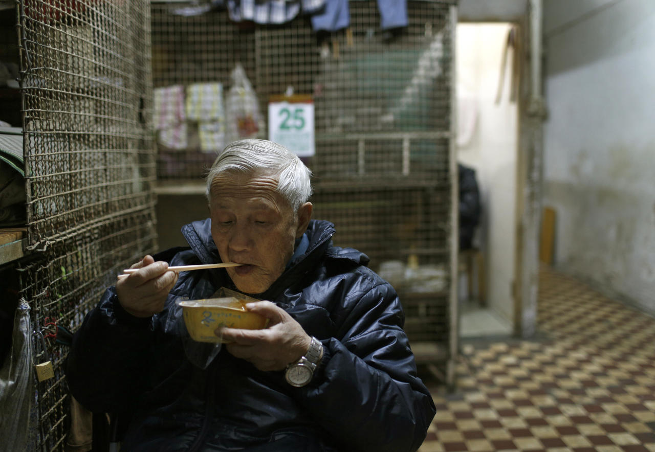 In this Jan. 25, 2013 photo, 77-year-old Yeung Ying Biu eats next to the cage, measuring 1.5 square meters (16 square feet), he calls home, in Hong Kong. For many of the richest people in Hong Kong, one of Asia's wealthiest cities, home is a mansion with an expansive view from the heights of Victoria Peak. For some of the poorest, home is a metal cage. Some 100,000 people in the former British colony live in what's known as inadequate housing, according to the Society for Community Organization, a social welfare group. (AP Photo/Vincent Yu)