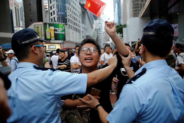 <p>A pro-China supporter is stopped by police as he tries to get closer to pro-democracy supporters during a march marking the 20th anniversary of Hong Kong's handover to Chinese sovereignty from British rule, in Hong Kong, China, July 1, 2017. (Photo: Damir Sagolj/Reuters) </p>