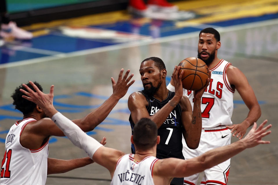 Brooklyn Nets forward Kevin Durant (7) looks to pass around Chicago Bulls forward Thaddeus Young, left, during the second half of an NBA basketball game Saturday, May 15, 2021, in New York. (AP Photo/Adam Hunger)