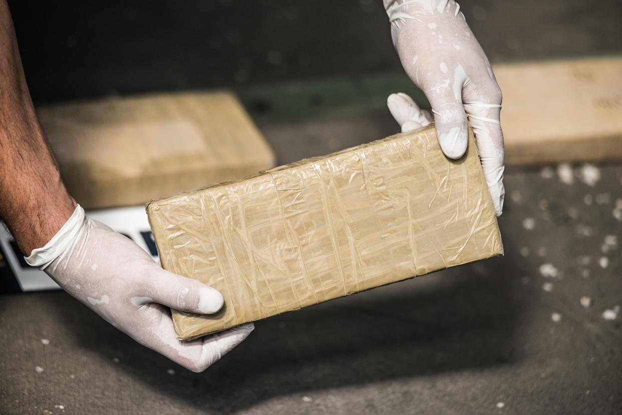 Investigator hands showing a package containing illegal drugs