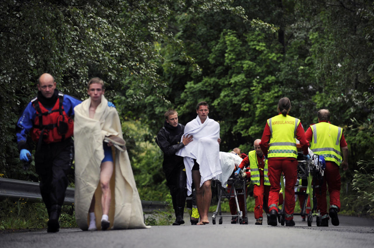 Medics and emergency workers escort youths from a camp site on the island of Utoya, Norway Saturday July 23, 2011. A Norwegian dressed as a police officer gunned down at least 84 people at an island retreat, police said Saturday. Investigators are still searching the surrounding waters, where people fled the attack, which followed an explosion in nearby Oslo that killed seven. (AP Photo/Morten Edvardsen/Scanpix