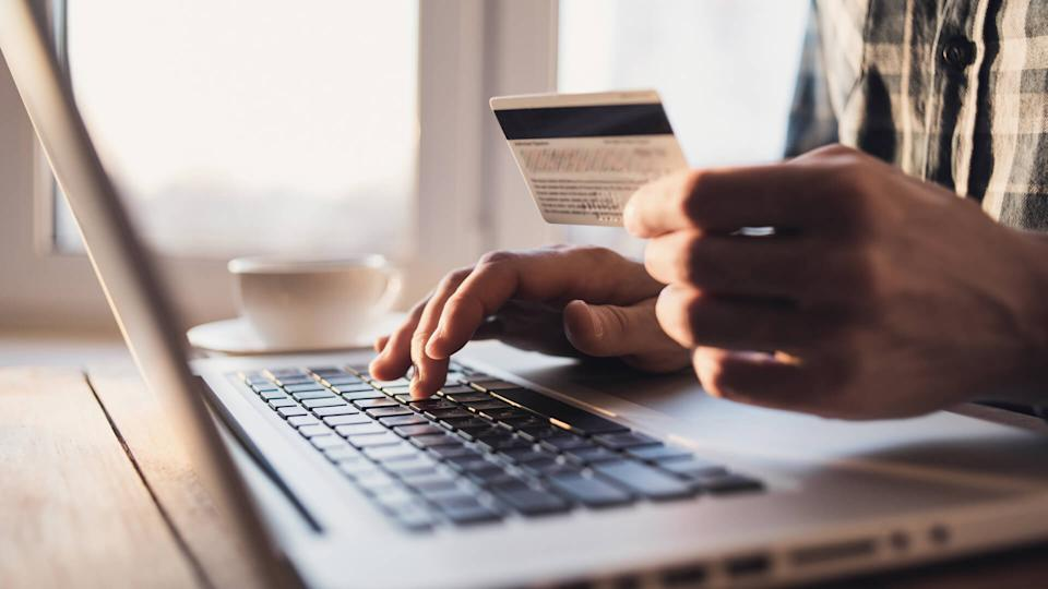 Man holding credit card and using laptop.