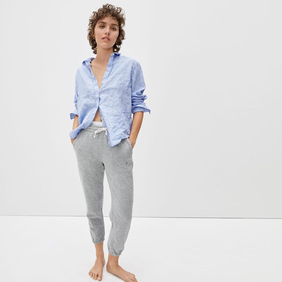 Model wears The Lightweight French Terry Jogger in grey with a blue collared shirt. Image via Everlane.