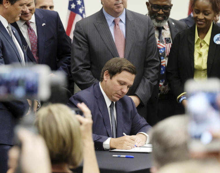 Florida Gov. Ron DeSantis signs the Sanctuary City bill Friday, June 14, 2019 at the Okaloosa County, Fla., Commission Chambers in Shalimar Fla. The bill requires all law enforcement agencies in Florida to cooperate with federal immigration authorities. (Michael Snyder/Northwest Florida Daily News via AP)