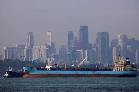 Oil tankers pass the skyline of Singapore