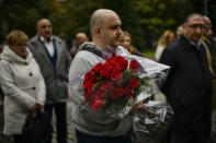 Spanish Basque socialist holds a red rose tribute for people killed during the Spanish Cvil War on the day that the remains of late Spanish dictator Francisco Franco are to be exhumed, in the basque city of Vitoria, northern Spain, Thursday, Oct. 24 2019. Forty-four years after his demise, the remains of Spanish dictator Gen. Francisco are to be dug out of his grandiose resting place outside Madrid and taken to a small family crypt, finally satisfying a long-standing demand of his victims' relatives and others who suffered under his regime. (AP Photo/Alvaro Barrientos)