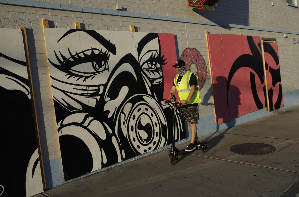 In this April 22, 2020, photo, a man in a mask rides a scooter by coronavirus inspired artwork on plywood covering the doors and windows of a temporarily shuttered donut shop in Las Vegas. (AP Photo/John Locher)