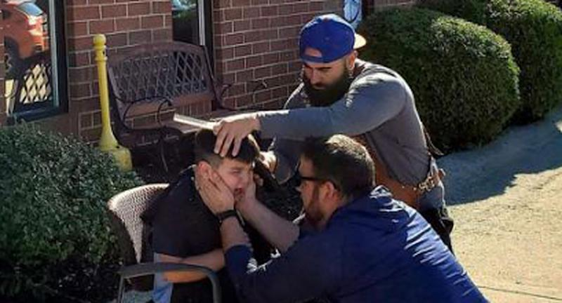 Bryce Juby, 7, gets his haircut by Marco Conti outside Marky Fresh Barbershop while his father Joe holds his face to comfort him.
