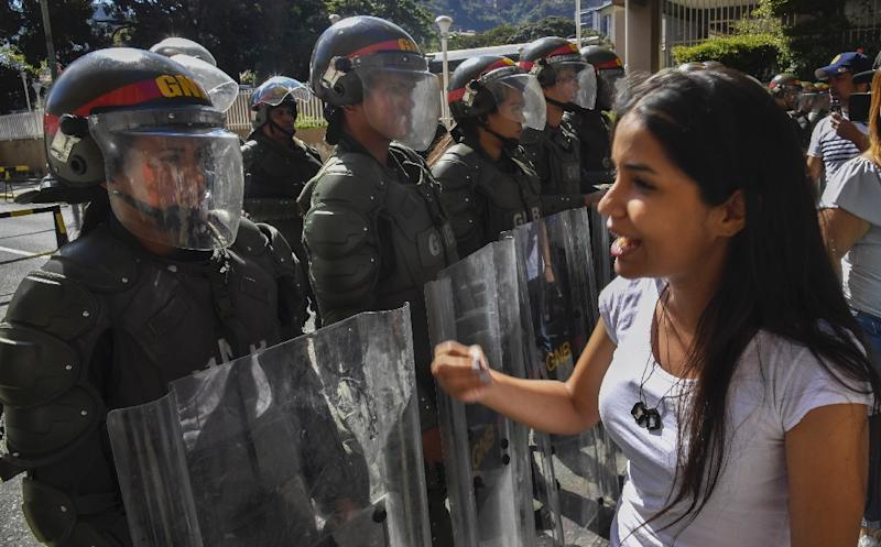 National guard members seen in Caracas as supporters of opposition leader Juan Guaido hand out leaflets offering amnesty to members of the military who defect to his camp (AFP Photo/Yuri CORTEZ)