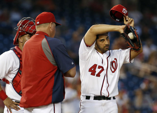 Washington Nationals starting pitcher Gio Gonzalez (47) wipes his head as he listens to pitching coach Steve McCatty (54), with catcher Sandy Leon, left, during the fourth inning of an interleague baseball game against the Houston Astros at Nationals Park Wednesday, June 18, 2014, in Washington. (AP Photo/Alex Brandon)