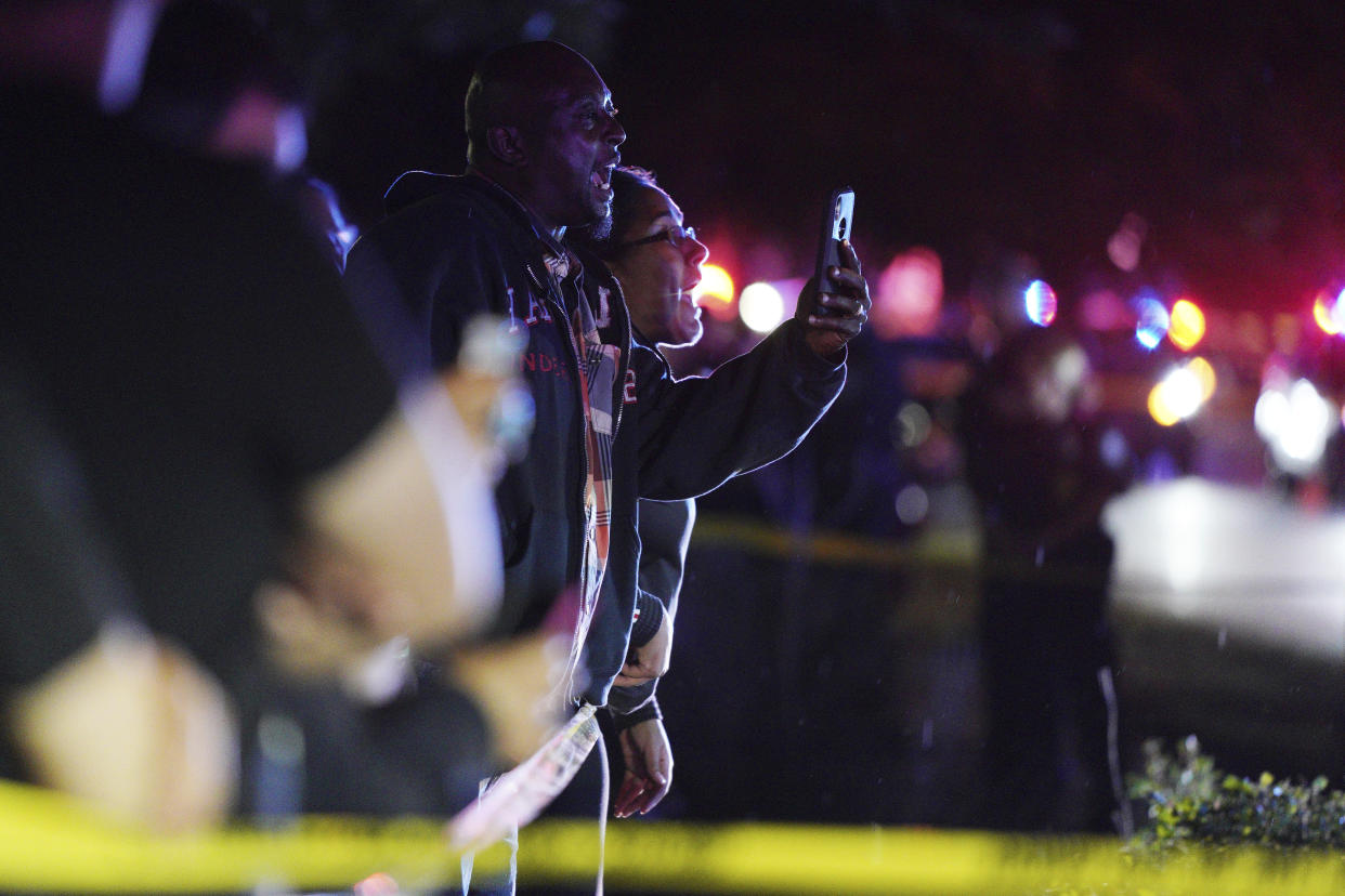 A person take pictures with a cell phone at the scene of an officer involved shooting  on East 77th Street in Richfield, Minn., Saturday night, Sept. 7, 2019. Police near Minneapolis shot and killed a driver following a chase after he apparently emerged from his car holding a knife and refused their commands to drop it. The chase started late Saturday night in Edina and ended in Richfield with officers shooting the man, Brian J. Quinones, who had streamed himself live on Facebook during the chase. (Anthony Souffle/Star Tribune via AP)