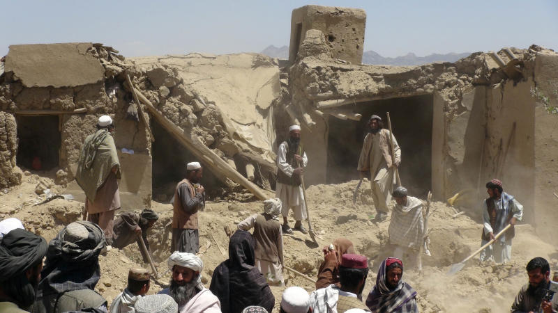 "FILE - In this Wednesday, June 6, 2012 file photo, Afghan villagers gather near a house destroyed in an apparent NATO raid in Logar province, south of Kabul, Afghanistan. It was once President Barack Obama's ""war of necessity."" Now, it's America's forgotten war. The Afghan conflict generates barely a whisper on the U.S. presidential campaign trail. It's not a hot topic at the office water cooler or in the halls of Congress _ even though 88,000 American troops are still fighting here and dying at a rate of one a day. (AP Photo/Ihsanullah Majroh, File)"