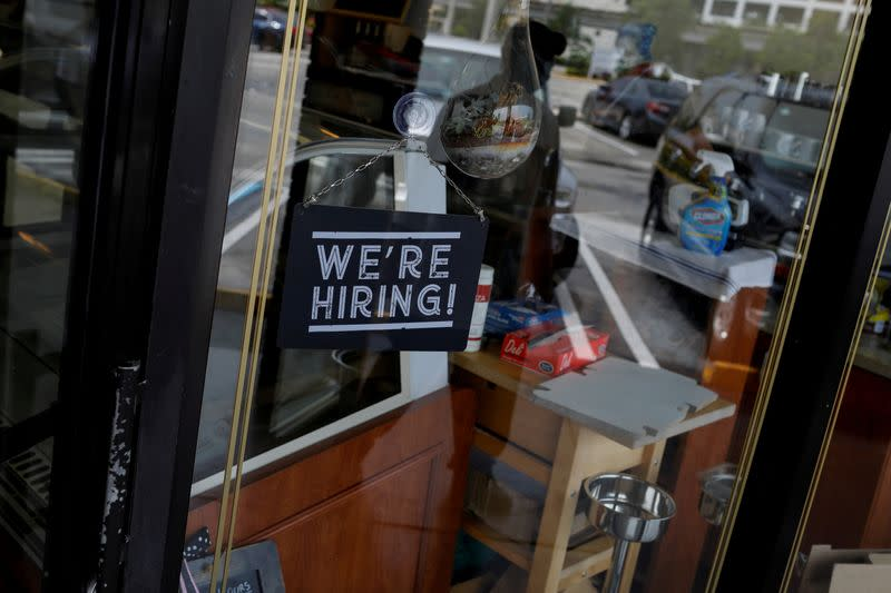 """FILE PHOTO: A """"We're Hiring"""" sign advertising jobs is seen at the entrance of a restaurant in Miami"""