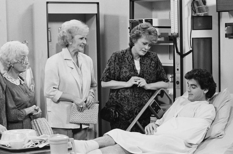George Clooney (bottom right) played a detective on the Golden Girls in 1987. Pictured from L-R: Estelle Getty, Betty White, Rue McClanahan. (Photo: Ron Tom/NBCU Photo Bank)