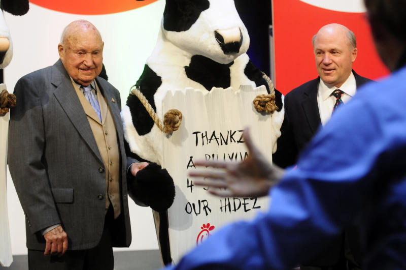 In this Monday, Dec. 14, 2009 picture, Chick-fil-a founder Truett Cathy, left, and his son Dan Cathy pose for a photo with the Chick-fil-A cows during a celebration of passing the $3 billon dollar mark in system-wide sales for the first time at the Chick-fil-a headquarters in Atlanta. Chick-fil-A, whose founder distinguished the fast-food chain by closing on Sunday out of religious piety, continues to mix theology with business and finds itself on the front lines of the nation's culture wars after its president, Dan Cathy, confirmed his opposition to gay marriage in June 2012. (AP Photo/Atlanta Journal-Constitution, Elissa Eubanks)