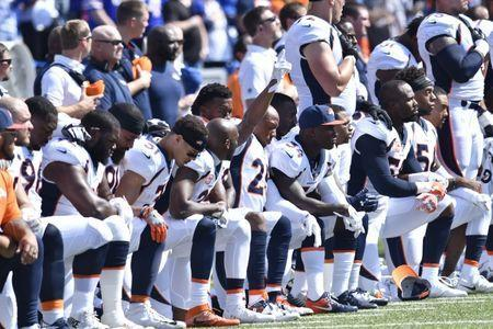 Sep 24, 2017; Orchard Park, NY, USA; Denver Broncos free safety Bradley Roby (29) raises his arm as other players kneel during the playing of the national anthem at New Era Field. Mandatory Credit: Mark Konezny-USA TODAY Sports
