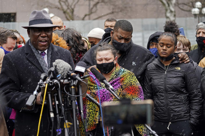 Katie Wright, center, the mother of Daunte Wright, and other family and friends gather during a news conference Tuesday, April 13, 2021, in Minneapolis as family attorney Ben Crump, left, speaks. Daunte Wright, 20, was shot and killed by police Sunday after a traffic stop in Brooklyn Center, Minn. (AP Photo/Jim Mone)